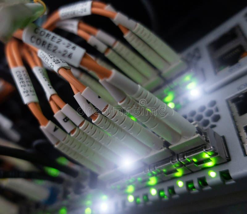 Feche acima do cabo de fibra ótica Cremalheiras dos servidores Separa o computador em uma cremalheira no grande centro de dados foto de stock