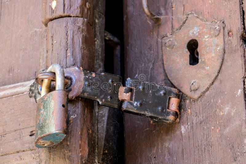 Feche acima do cadeado e do ferrolho velho em uma porta de madeira velha foto de stock