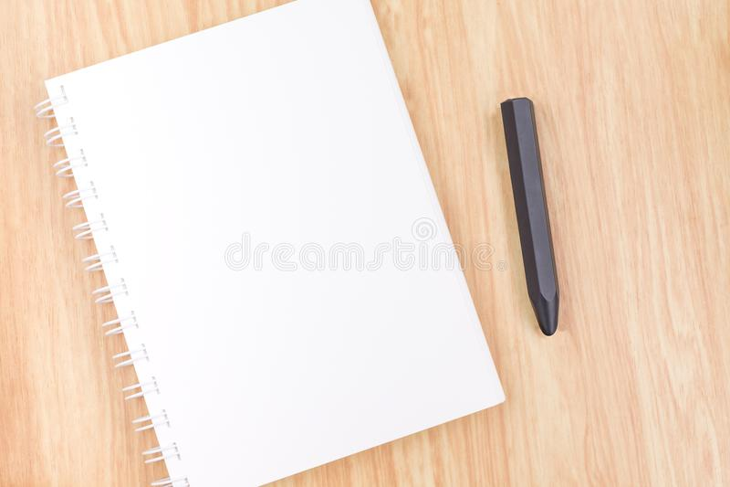 Feche acima do caderno aberto da pasta de anel da placa com o lápis preto no wo imagens de stock
