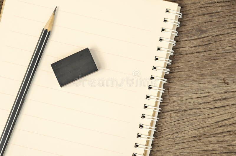 Feche acima do caderno com lápis e eliminador na parte superior fotos de stock