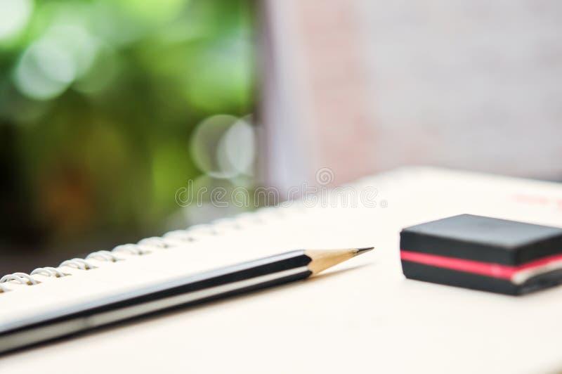 Feche acima do caderno com lápis e eliminador na parte superior imagem de stock