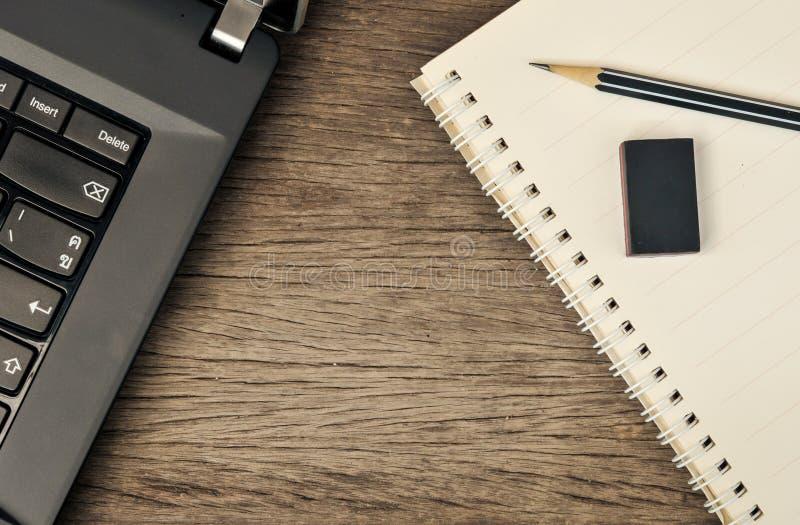 Feche acima do caderno com lápis e eliminador na parte superior foto de stock