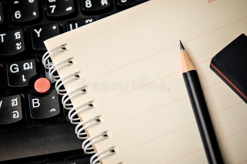 Feche acima do caderno com lápis e eliminador na parte superior fotos de stock royalty free
