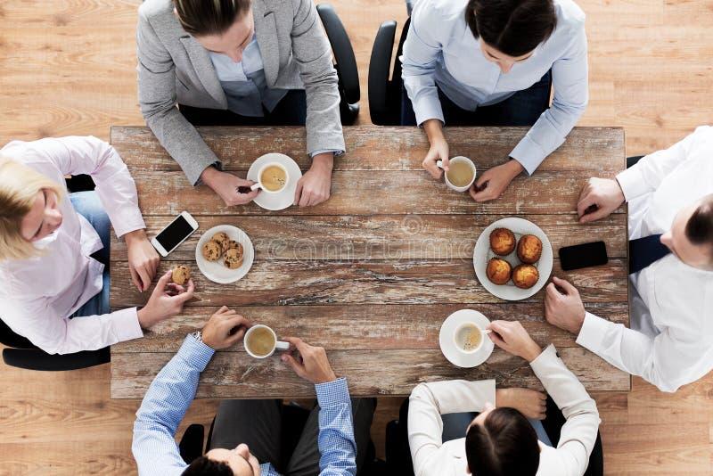 Feche acima do café bebendo da equipe do negócio no almoço imagem de stock royalty free