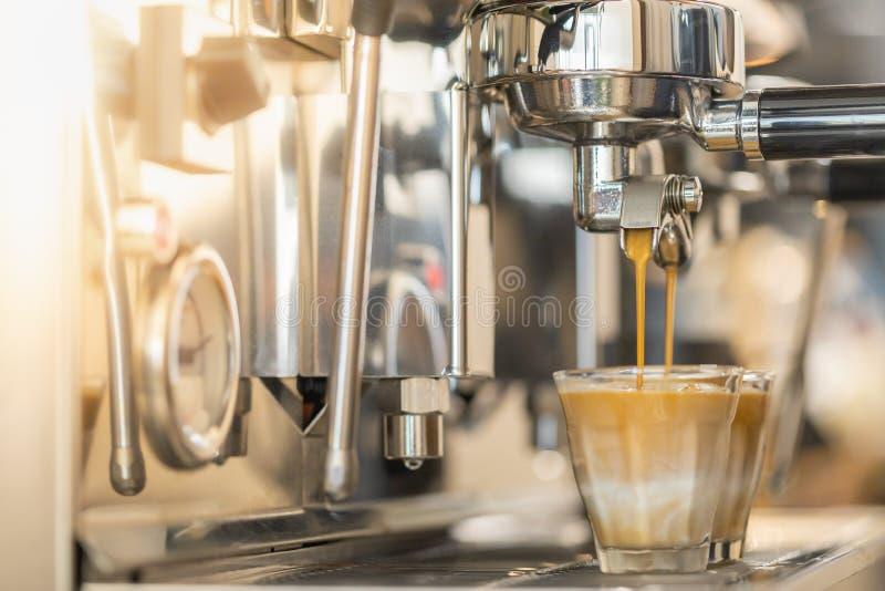 Feche acima do café que derrama da máquina automática do café a dois que o leite disparou no vidro no restaurante imagens de stock royalty free