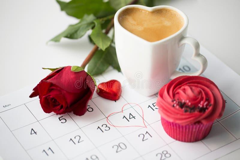Feche acima do calendário, do café, do queque e da rosa vermelha fotografia de stock royalty free