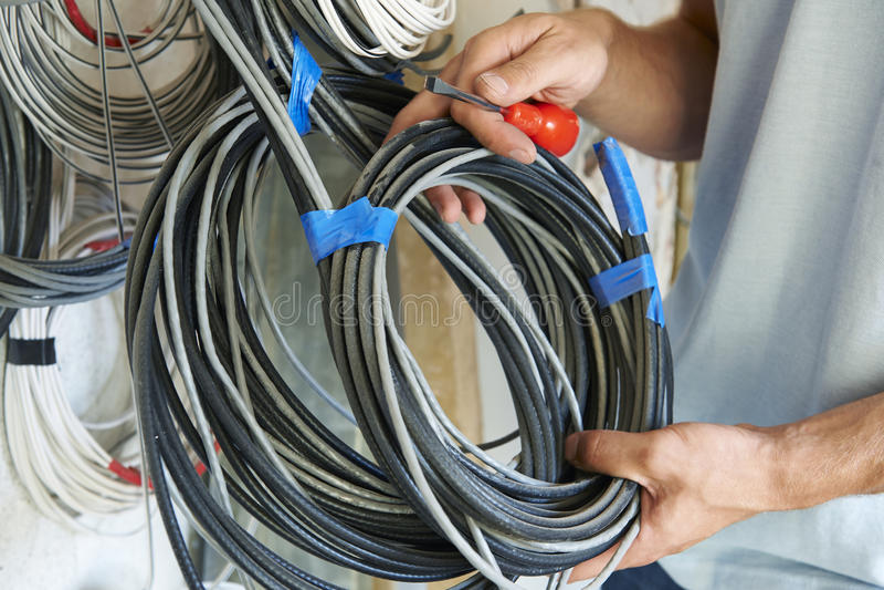Feche acima do canteiro de obras de Fitting Wiring On do eletricista foto de stock