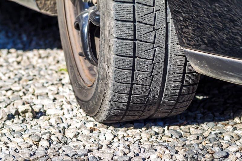 Feche acima do car& x27; passo do pneumático do inverno de s na estrada do cascalho imagens de stock royalty free