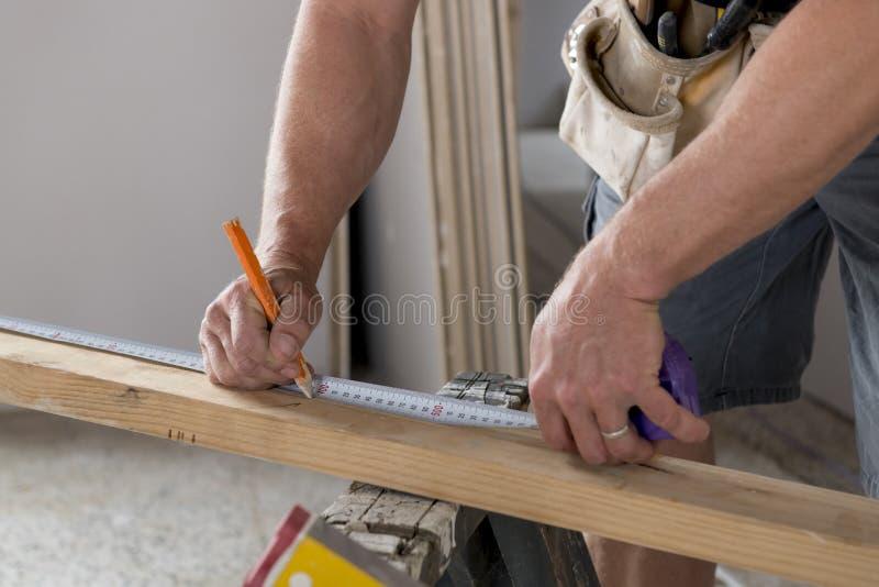 Feche acima do carpinteiro masculino do construtor ou da madeira de trabalho e de medição do detalhe das mãos do construtor no co fotografia de stock royalty free
