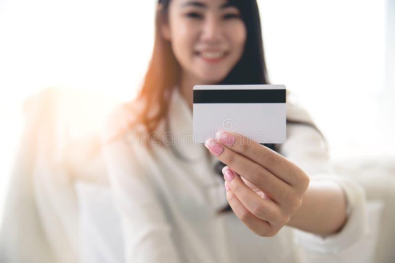 Feche acima do cartão de crédito que guarda pela mulher asiática da beleza Conceito da compra em linha e do pagamento fácil fotos de stock royalty free