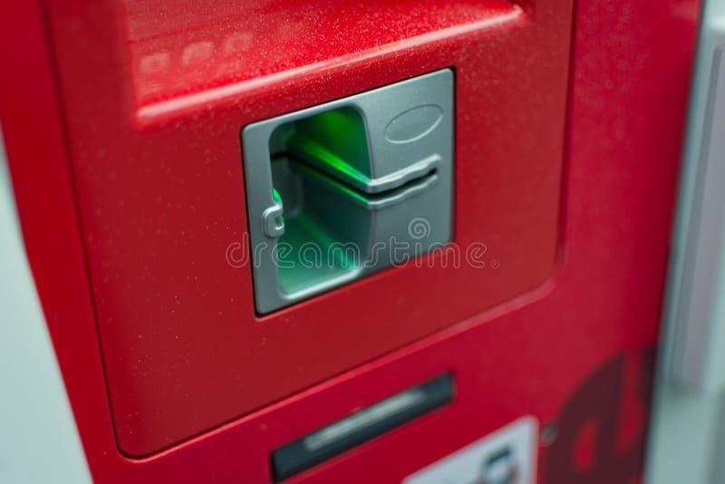 Feche acima do cartão vermelho da inserção da máquina do atm aqui fotografia de stock royalty free