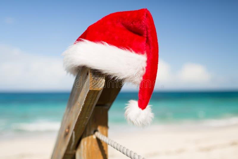 Feche acima do chapéu do ajudante de Santa na praia imagens de stock
