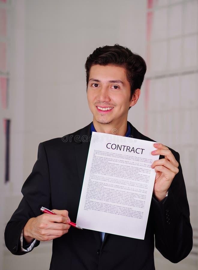 Feche acima do chefe de sorriso que veste um terno e que dá uma folha de papel do texto do contrato nela, e guardando uma pena pa imagens de stock royalty free