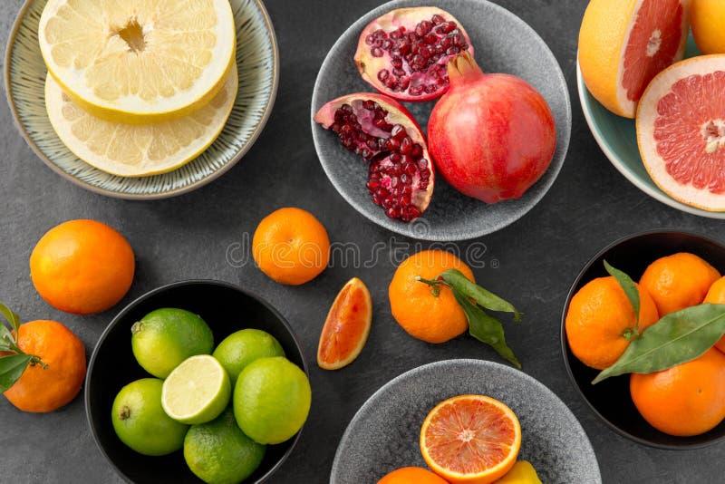 Feche acima do citrino em frutos das bacias na tabela de pedra foto de stock