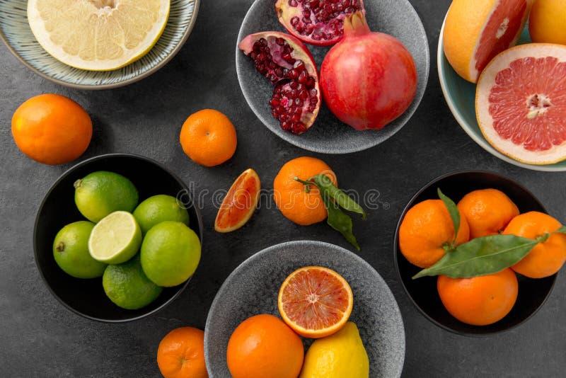 Feche acima do citrino em frutos das bacias na tabela de pedra foto de stock royalty free