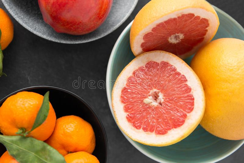 Feche acima do citrino em frutos das bacias na tabela de pedra fotografia de stock