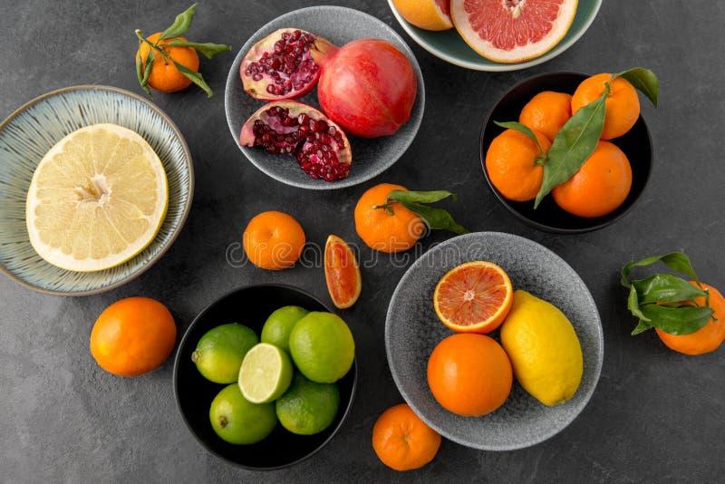 Feche acima do citrino em frutos das bacias na tabela de pedra imagem de stock