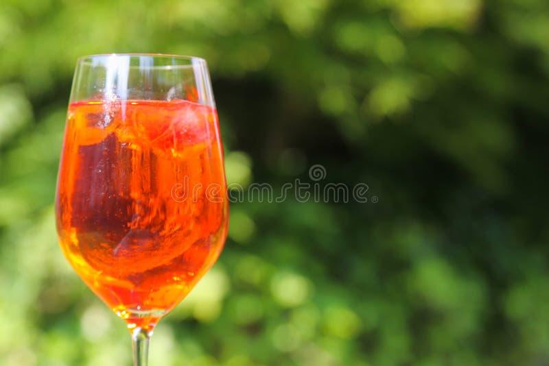 Feche acima do cocktail alaranjado vermelho no vidro de vinho com os cubos de gelo contra o fundo das plantas verdes foto de stock