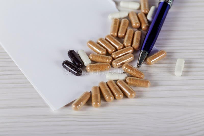 Feche acima do comprimido da vitamina na tabela de madeira, conceito saudável imagens de stock royalty free