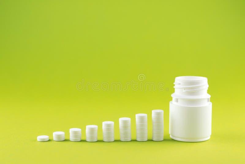 Feche acima do conceito da pirâmide dos comprimidos brancos e engarrafe no fundo do amarelo da pera com espaço da cópia Foco no p imagens de stock