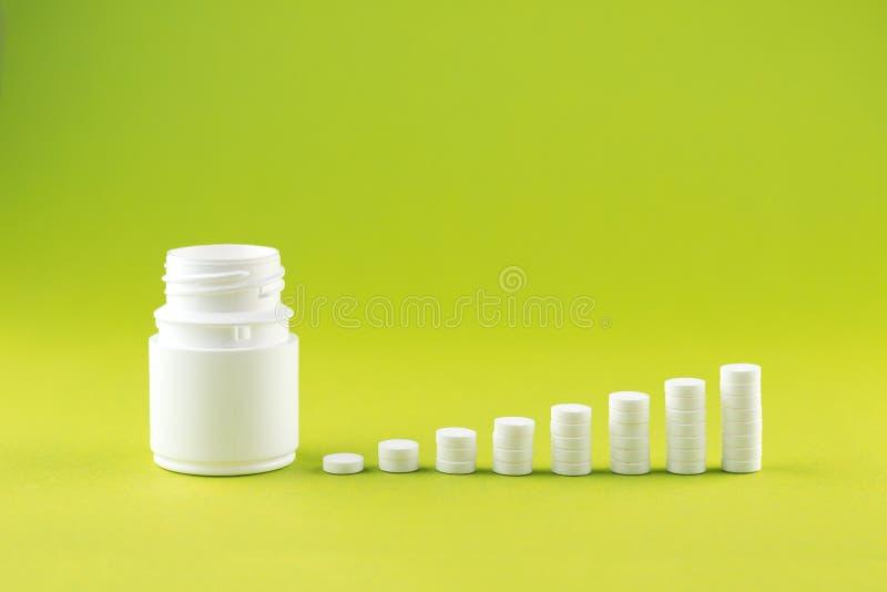 Feche acima do conceito da pirâmide dos comprimidos brancos e engarrafe no fundo do amarelo da pera com espaço da cópia Foco no p foto de stock