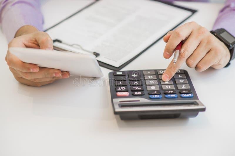 Feche acima do contador ou do banqueiro masculino que fazem cálculos Economias, finanças e conceito da economia fotos de stock
