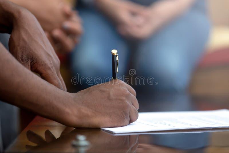 Feche acima do contrato de assinatura do homem negro que põe a assinatura foto de stock royalty free