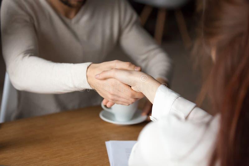 Feche acima do contrato de assinatura do relator do aperto de mão do marido no café fotos de stock royalty free