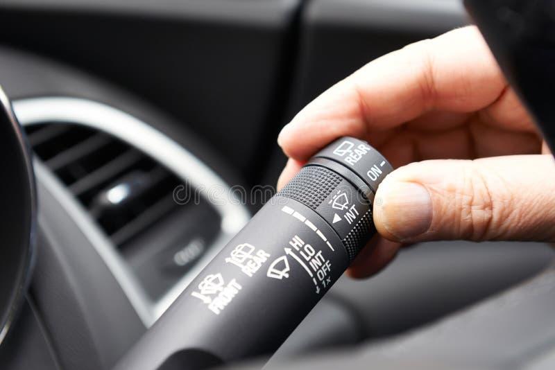 Feche acima do controle de funcionamento do limpador de pára-brisas da mão no carro fotografia de stock royalty free