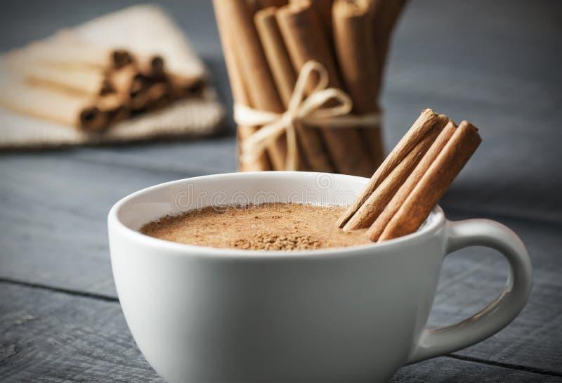Feche acima do copo branco da bebida quente leitosa do salep de Turquia com a especiaria saudável do pó da canela foto de stock