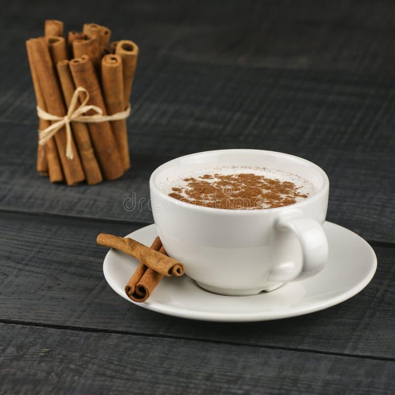 Feche acima do copo branco da bebida quente leitosa do salep de Turquia com a especiaria saudável do pó da canela no preto foto de stock royalty free