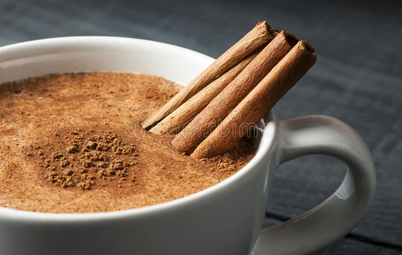 Feche acima do copo branco da bebida quente leitosa do salep de Turquia com pó da canela foto de stock