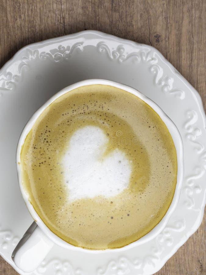 Feche acima do copo de caf? branco com arte do latte da forma do cora??o na tabela de madeira no caf? fotografia de stock