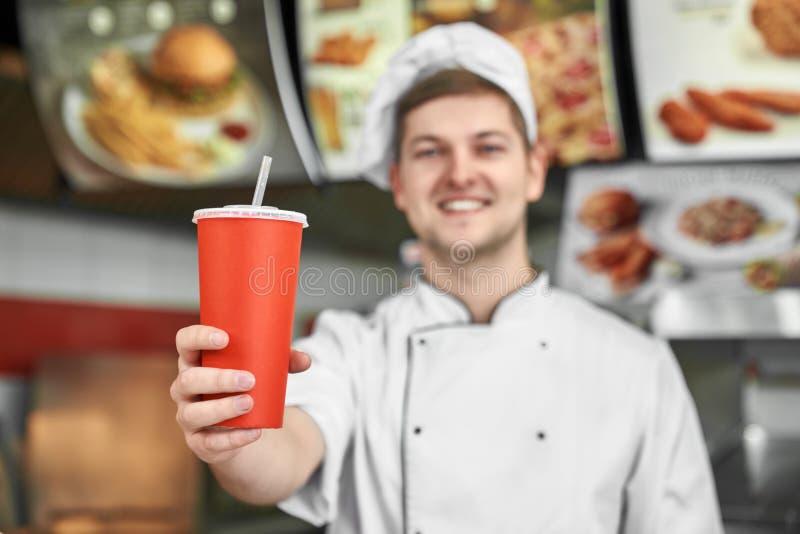 Feche acima do copo de papel vermelho Cozinheiro chefe alegre que propõe a bebida foto de stock royalty free