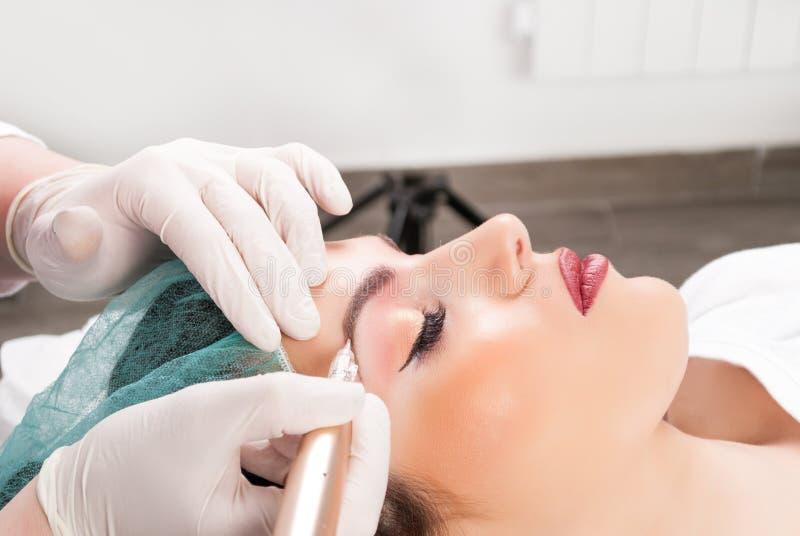 Feche acima do cosmetologist que aplica o permanent compõem nas sobrancelhas fêmeas foto de stock