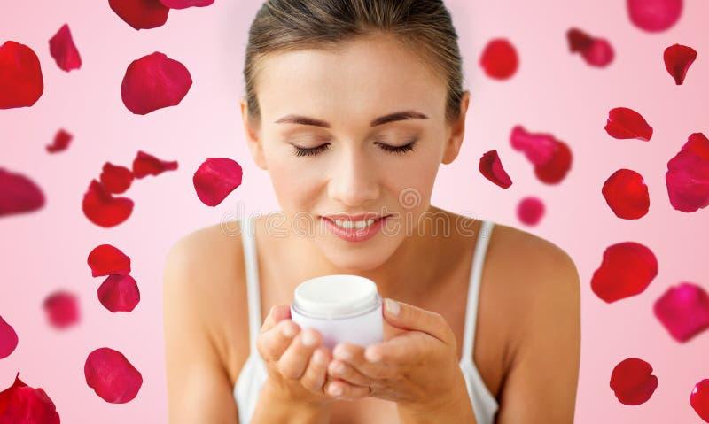 Feche acima do creme de cheiro da mulher sobre as pétalas cor-de-rosa fotografia de stock royalty free