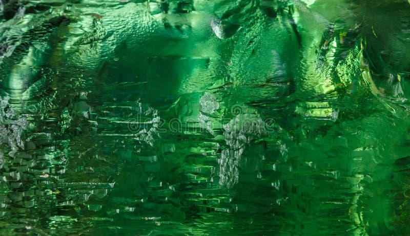 Feche acima do cristal cortado na luz esmeralda misteriosa Fundo brilhante mágico Sumário imagem de stock