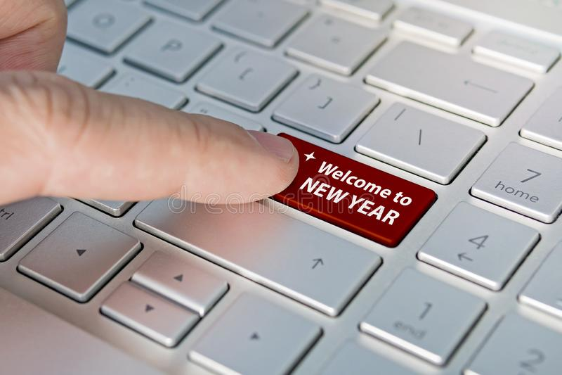 Feche acima do dedo no botão do teclado com palavra BEM-VINDA do ANO NOVO Um dedo masculino pressiona um botão da cor em um tecla imagem de stock