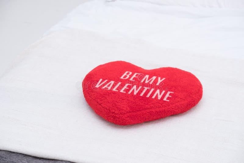 Feche acima do descanso vermelho do coração com seja minha palavra do Valentim que encontra-se na cama fotos de stock royalty free
