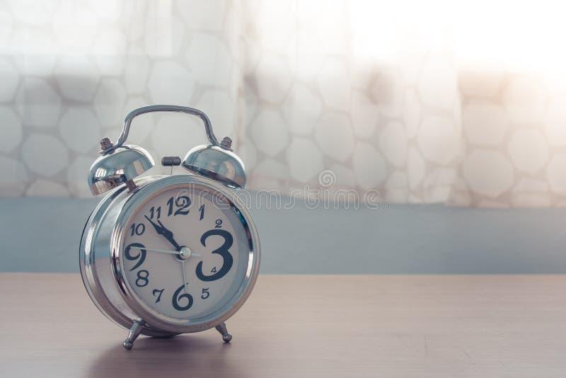 Feche acima do despertador de prata velho na tabela de madeira no quarto com a cortina branca no fundo fotografia de stock