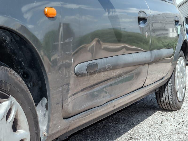 Feche acima do detalhe de uma porta amolgada do motorista de um acidente de viação ou de um acidente de automóvel fotografia de stock