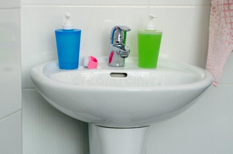 Feche acima do dissipador, da torneira e dos acessórios modernos do banheiro fotografia de stock