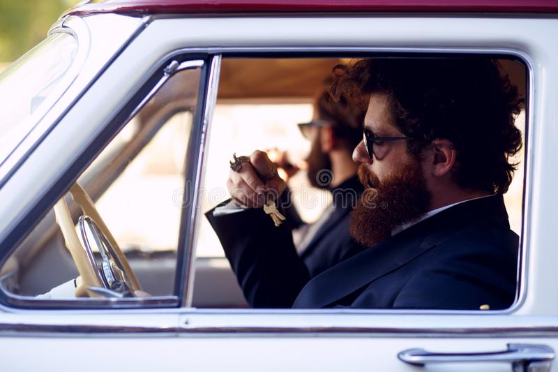 Feche acima do dois homens farpados, nos óculos de sol e nos ternos elegantes pretos, fumando cigarros para dentro do carro do vi imagem de stock royalty free