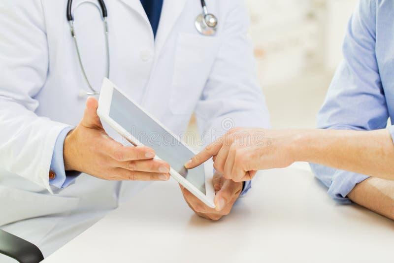 Feche acima do doutor e do paciente masculinos com PC da tabuleta imagens de stock royalty free
