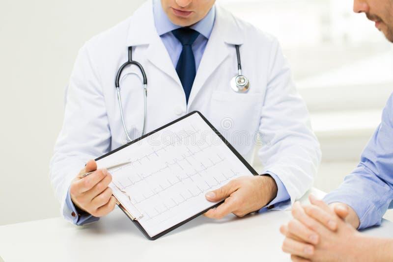 Feche acima do doutor e do paciente masculinos com prancheta imagens de stock royalty free