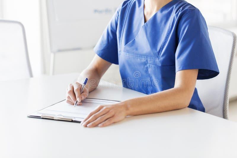 Feche acima do doutor ou da enfermeira que escrevem à prancheta fotos de stock