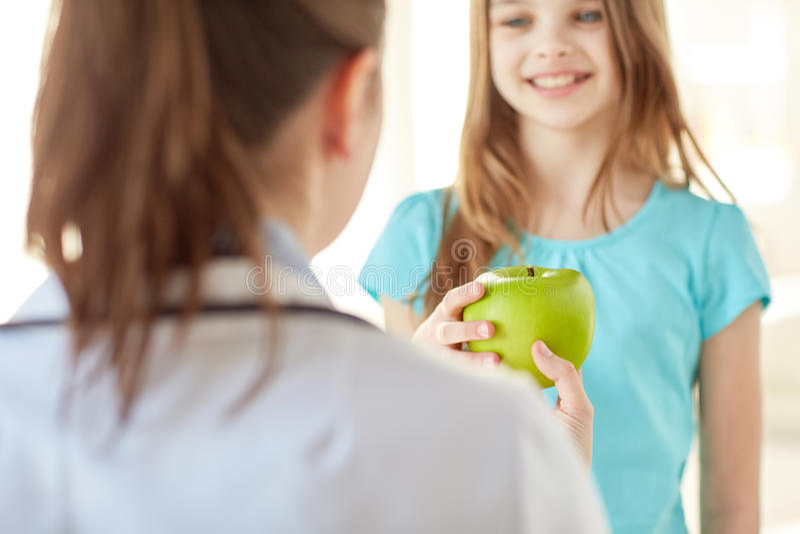 Feche acima do doutor que dá a maçã à menina feliz fotografia de stock royalty free