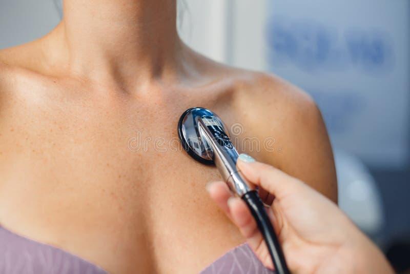 Feche acima do doutor que usa o estetoscópio ao coração do paciente da mulher do exame fotografia de stock