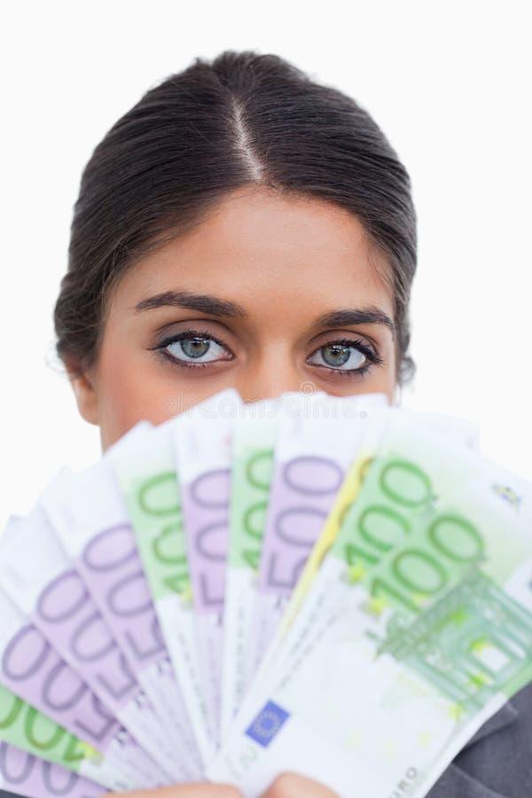 Feche acima do empresário fêmea que esconde sua cara atrás do dinheiro fotos de stock royalty free