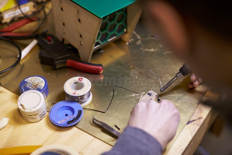 Feche acima do engenheiro eletrotécnico Soldering Circuit Board fotografia de stock royalty free